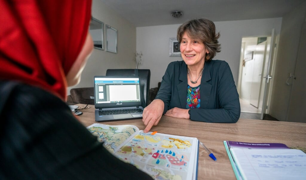 Caroline Stel begeleidt de 13-jarige Amal met haar huiswerk.  (beeld Jeroen Jumelet)