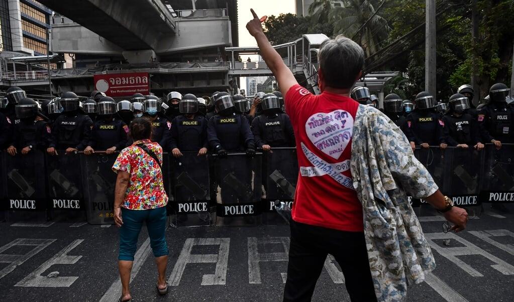 Demonstranten die in Myanmar de straat op gaan voor meer democratie stuiten op een muur aan politieagenten.  (beeld afp / Lillian Suwanrumpha)