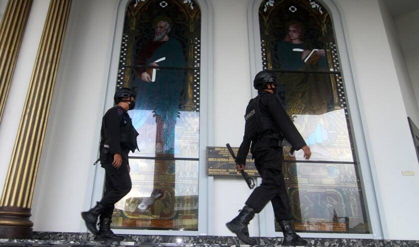Politiemannen in de kathedraal van Pontianak op Borneo waar op Palmzondag een zelfmoordaanslag plaatsvond.  (beeld afp / Andri Husen)