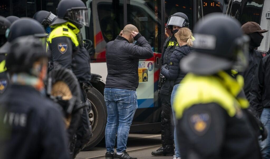 Actievoerders tegen de coronamaatregelen werden door de mobiele eenheid ingesloten en vervolgens in bussen weggevoerd.  (beeld anp / Jeroen Jumelet)