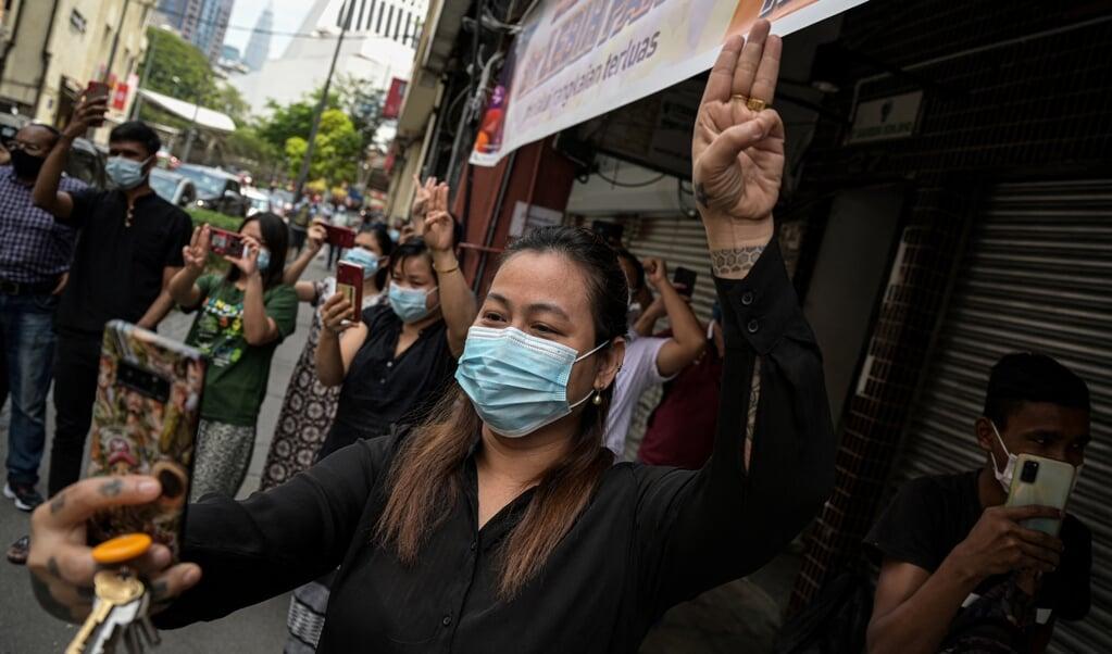 Een vrouw in Kuala Lumpur, aanhanger van de Nationale Liga voor Democratie in Myanmar, geeft een groet als statement tegen de militaire coup in Myanmar.  (beeld afp / Mohd Rasfan)