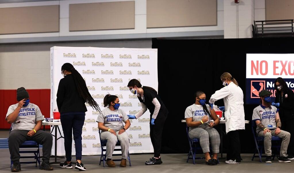Studenten zitten in de rij in een priklocatie in New York. De vaccinatiecampagne verloopt in de VS erg voorspoedig.  (beeld epa / Michael Santiago)