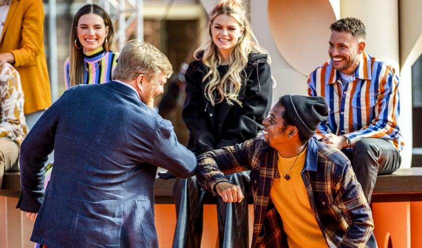 Koning Willem-Alexander geeft een elleboogje aan rapper Typhoon (rechts) tijdens de repetities van The Streamers. Vanaf het terrein van Paleis Noordeinde sloot de gelegenheidsband met een concert Koningsdag feestelijk af.  (beeld anp / royal images Sem van der Wal)
