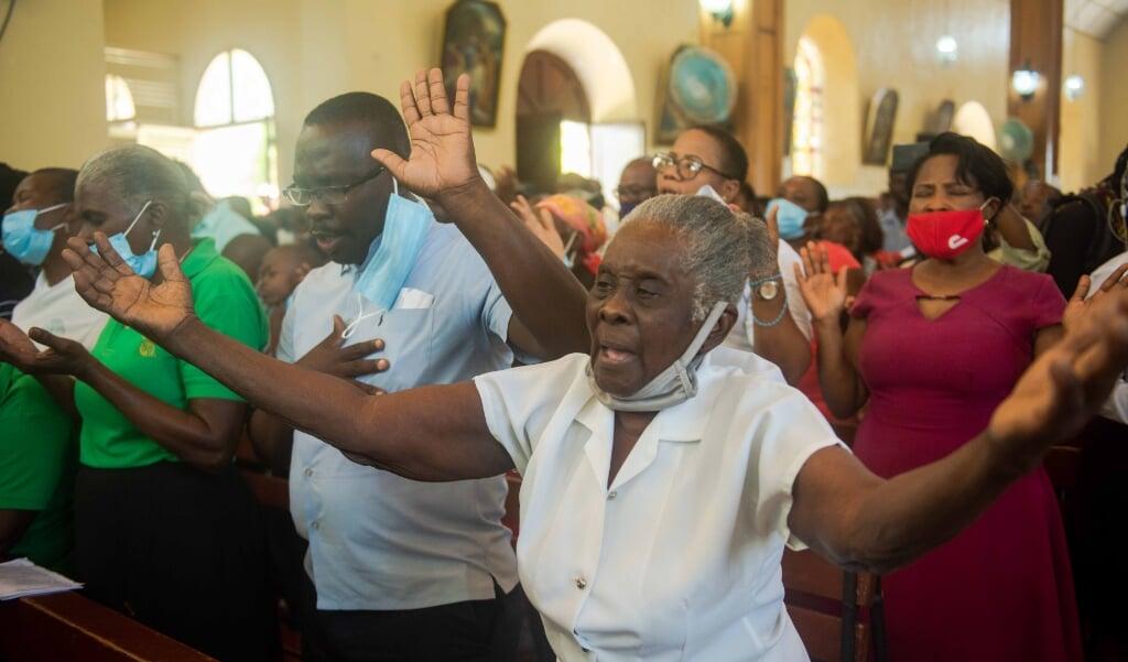 Katholieke gelovigen bidden in Port-au-Prince voor de vrijlating van de gegijzelden, waaronder meerdere priesters en vrouwelijke religieuzen.  (beeld Epa / Jean Marc Herve Abelard)