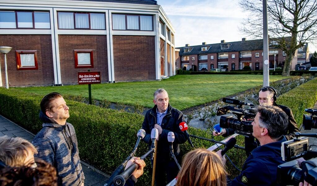 De hulpkoster en een kerkganger staan journalisten te woord bij de Mieraskerk in Krimpen aan den IJssel.  (beeld anp / Robin Utrecht)