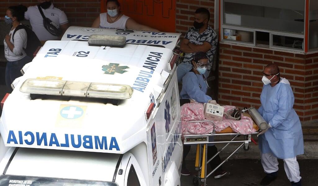 Een ambulance arriveert bij het ziekenhuis van de Colombiaanse hoofdstad Medellin. Het ziekenhuis kan het aantal coronapatiënten niet meer aan.  (beeld Epa / Luis Eduardo Noriega)