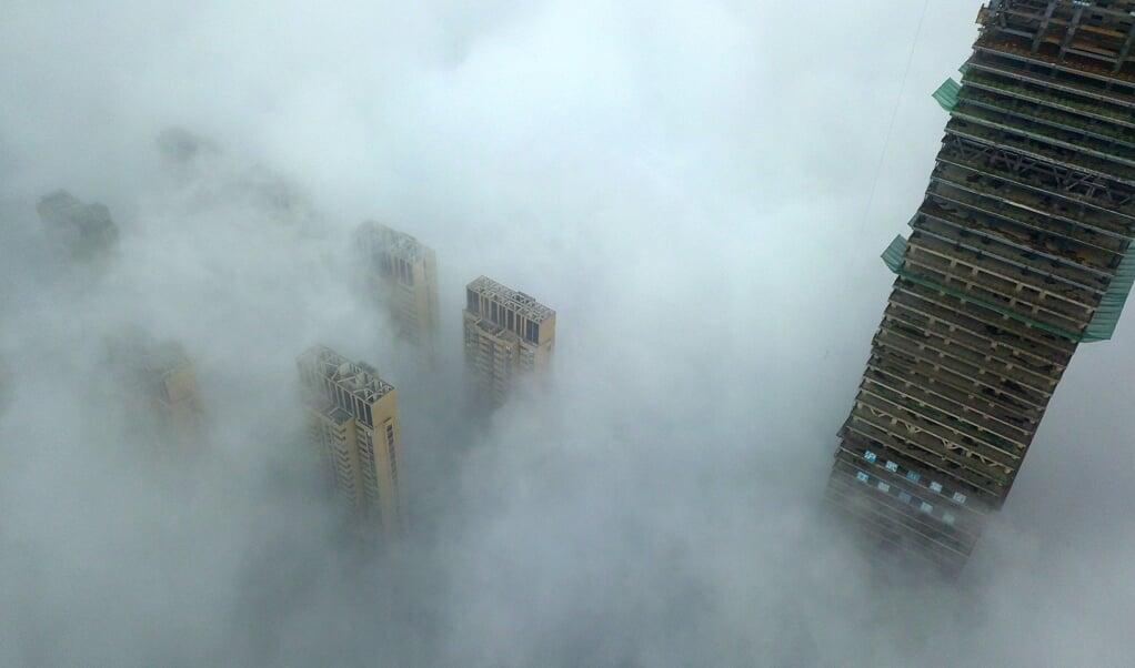 Smog rond hoogbouw in de Chinese stad Yangzhou. PwC wijst erop dat consumenten in bijvoorbeeld Azië meer worden geconfronteerd met de gevolgen van milieuvervuiling en klimaatverandering.  (beeld str / afp)