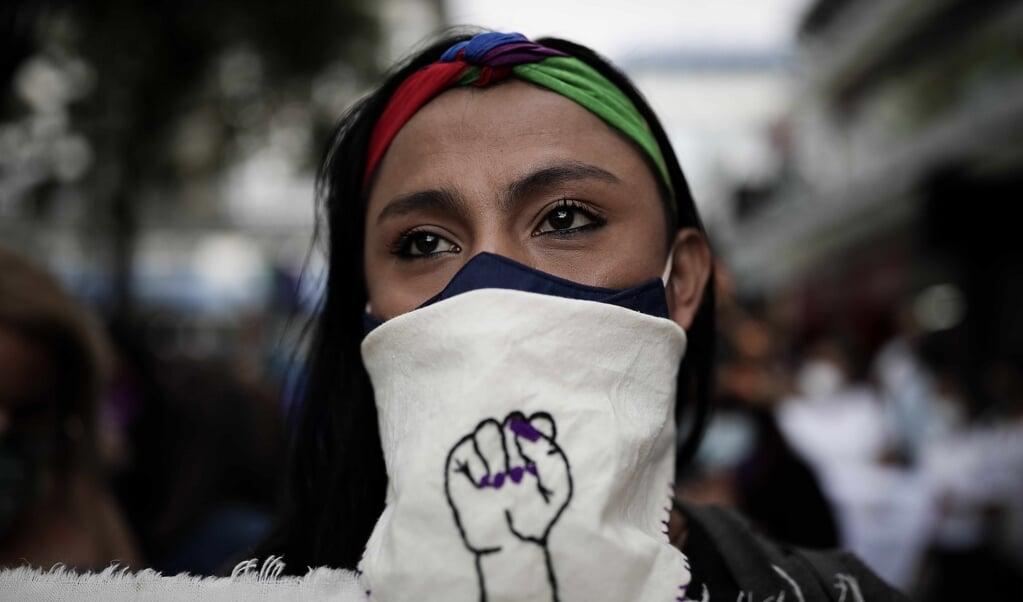Een vrouw kijkt toe terwijl honderden vrouwen door de straten van San Jose, Costa Rica, marcheren tijdens een protest tegen vrouwenmoorden, op Internationale Vrouwendag, 8 maart 2021.  (beeld epa / Jeffrey Arguedas)