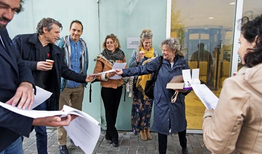 Bénédicte Ficq deelt bij het Paleis van Justitie exemplaren van de aangifte uit aan mede-ondertekenaars.   (beeld anp / Olaf Kraak)