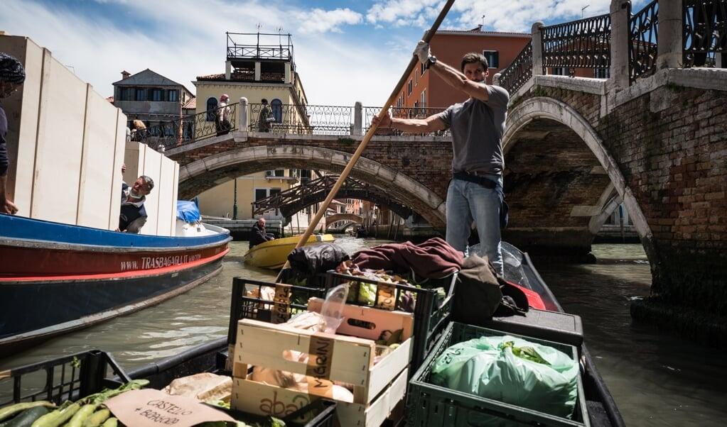 Federico Mantovan vaart, staand als een gondelier op zijn groenteboot, door de verlaten grachten van Venetië.  (beeld Nicola Zolin)