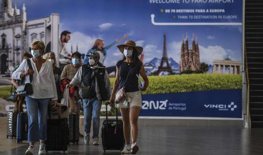 Vakantiegangers arriveren op het vliegveld van Faro in Portugal.  (beeld afp / Patricia de Melo Moreira)
