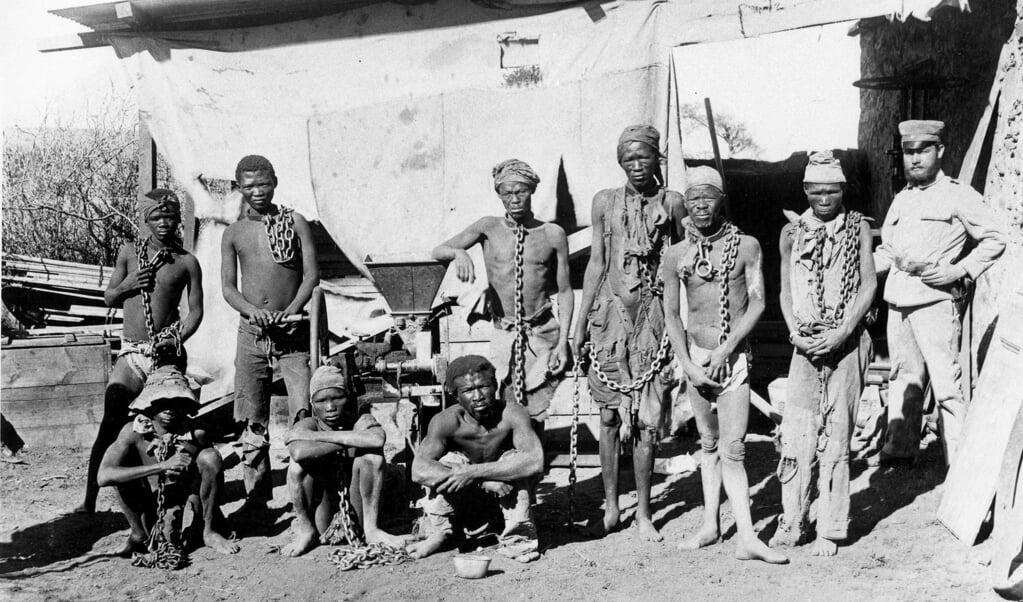 Gevangengenomen Herero- en Nama-mannen en een Duitse soldaat in de periode 1904-1908. Tachtigduizend Herero en Nama kwamen om het leven.  (beeld afp / National Archives of Namibia)