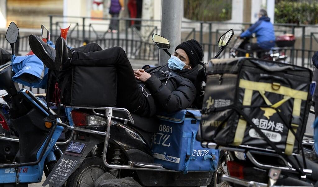Een koerier in Shanghai rust uit terwijl hij op een nieuwe bezorgorder wacht. Meer mensen werken meer dan 55 uur per week.  (beeld afp / Noel Celis)