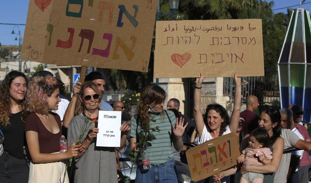 Met leuzen als 'Wij zijn broeders' en 'Arabieren en Joden weigeren vijanden te zijn' demonstreren inwoners van de gemengd Arabisch-Joodse stad Jish tegen de gewelddadige rellen van radicale  Arabische en Joodse groeperingen.   (beeld afp /Jalaa Marey)