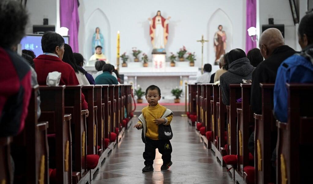 In een katholieke kerk in een dorp vlakbij de Chinese hoofdstad Beijing vierden gelovigen op 3 april het Paasfeest.  (beeld afp / Jade Gao)