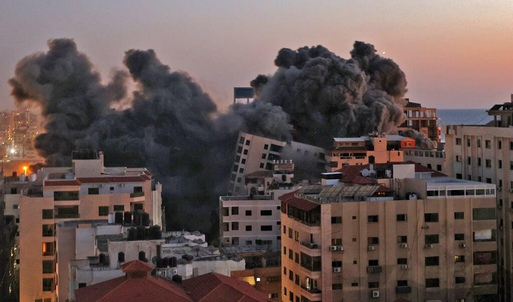 Grote roetwolken stegen dinsdag op uit de Gazastrook na een bombardement door het Israëlische leger.  (beeld afp / Mohammed Abed)