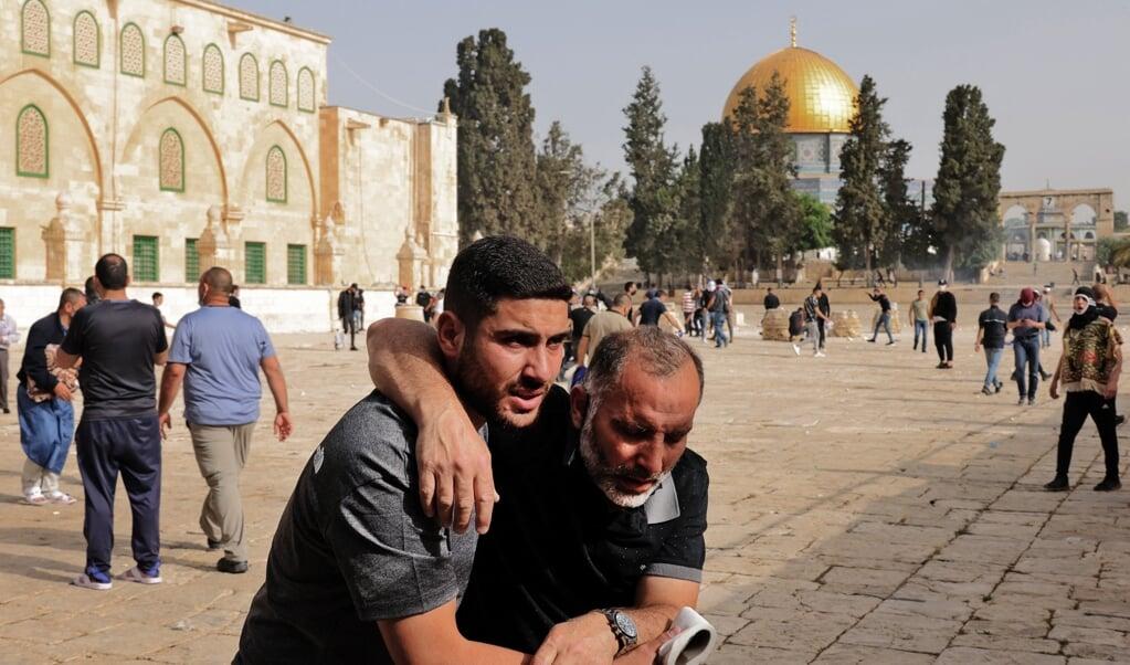 Een Palestijn helpt een man die gewond is geraakt bij een confrontatie met de Israëlische politie bij de Al-Aqsamoskee.   (beeld afp / Ahmad Gharabli)