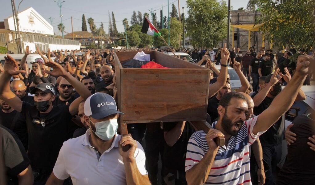 Israëlische Arabieren op 11 mei 2021 tijdens de begrafenis van een bij de een betoging omgekomen man in de stad Lod.   (beeld afp)