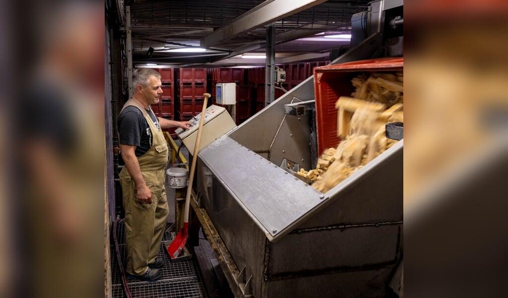 Een werknemer bedient een verwerkingsmachine voor toast.   (beeld Ines Vansteenkiste-Muylle)