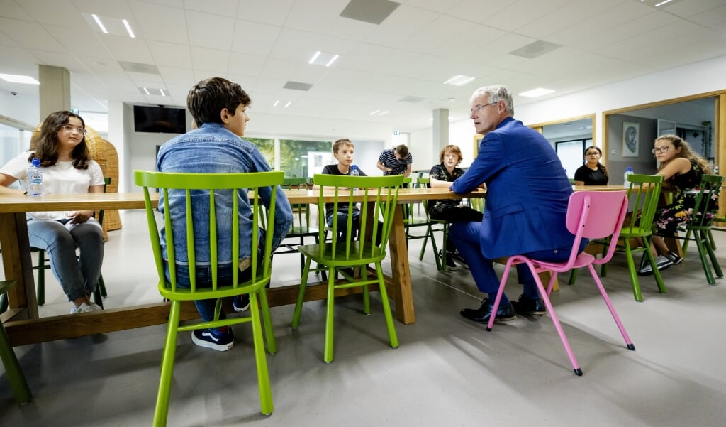 Minister Arie Slob (Basis- en Voortgezet Onderwijs en Media) praat met leerlingen tijdens de start van het schooljaar.  (beeld anp / Robin van Lonkhuijsen)
