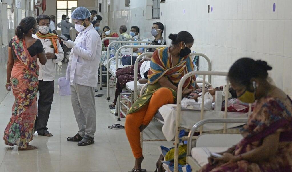 Een dokter spreekt met familieleden van een patiënt die herstellende is van corona. In India liggen de ziekenhuizen overvol met mensen die covid of de dodelijke 'zwarte schimmel'-ziekte onder de leden hebben.  (beeld afp / Noah Seelam)