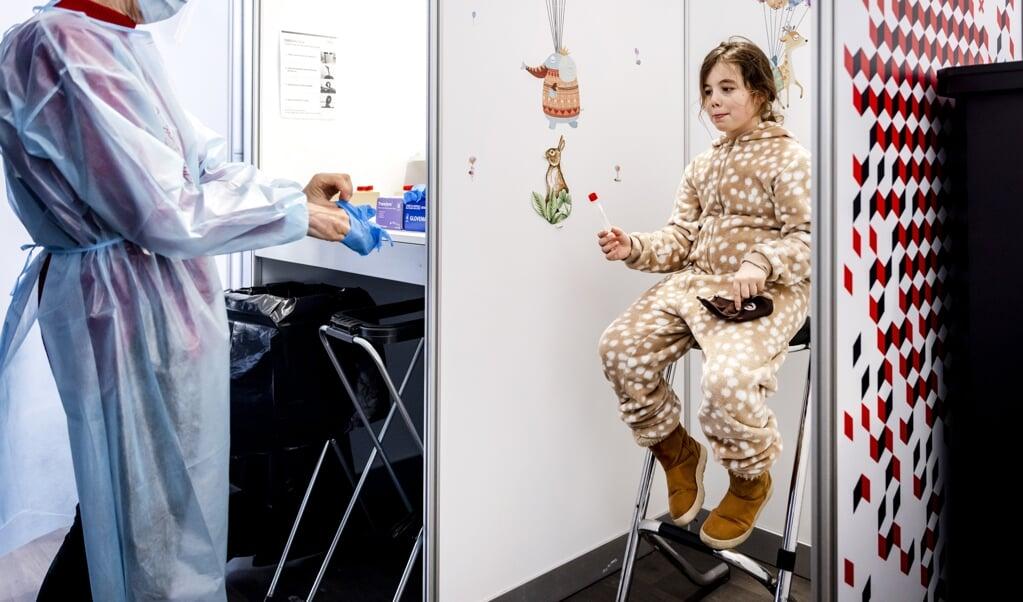 Een meisje ondergaat een coronatest op een locatie in Amsterdam. Als het gaat om vaccineren is Nederland doorgaans terughoudend.  (beeld anp / Remko de Waal)