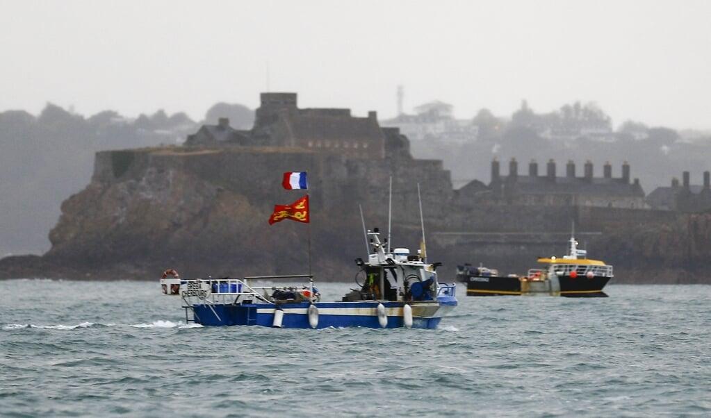 Franse vissers protesteren met hun schepen voor het Britse eiland Jersey.  (beeld afp / Sameer Al-Doumy)