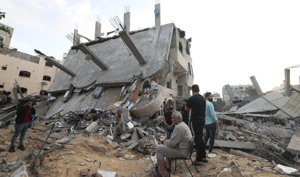 Palestijnen bij hun door Israël verwoeste huis in Beit Lahia op de Gazastrook. Israël antwoordde met luchtaanvallen na raketaanvallen vanuit de Gazastrook. Al dagen lopen de spanning in Israël en de Palestijnse gebieden op.  (beeld afp / Mahmud Hams)