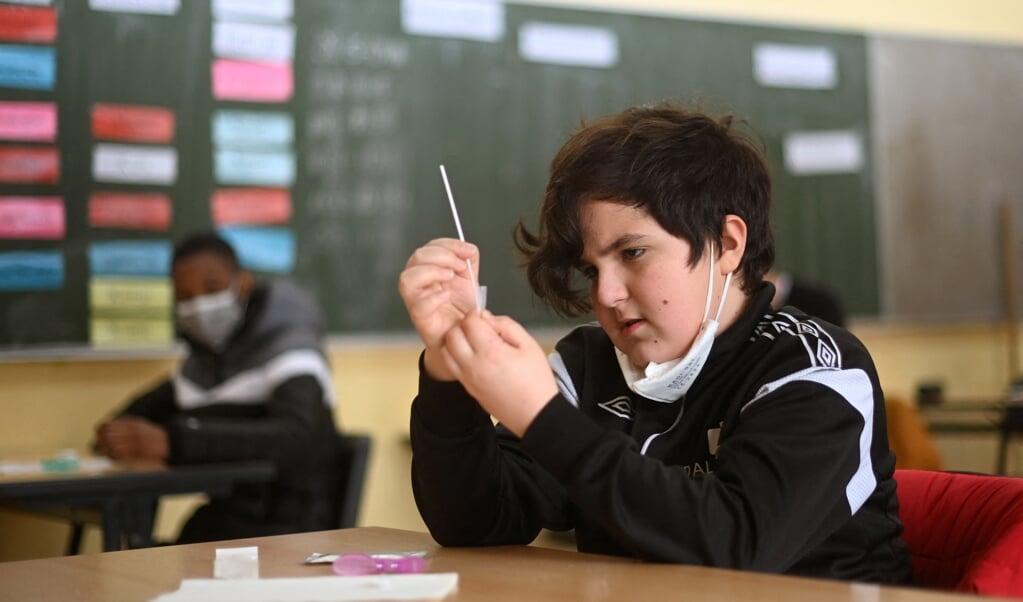 Een leerling oefent met een zelftest op een middelbare school in het Duitse Bonn. Ook in Nederland wil het OMT dat leerlingen trouw tweemaal per week een zelftest uitvoeren.  (beeld afp / Ina Fassbender)