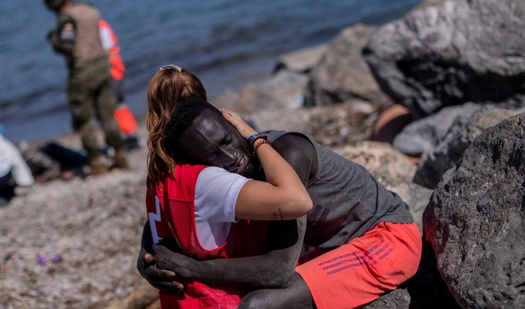 Rode Kruismedewerker Luna Reyes helpt een Senegalese migrant in het Spaanse deel van Marokko, Ceuta. Ze wordt geprezen om haar medemenselijkheid, maar ontving ook zo veel racistische en seksistische opmerkingen dat ze besloten heeft haar accounts op sociale media op te heffen.  (beeld Hollandse Hoogte / ap)