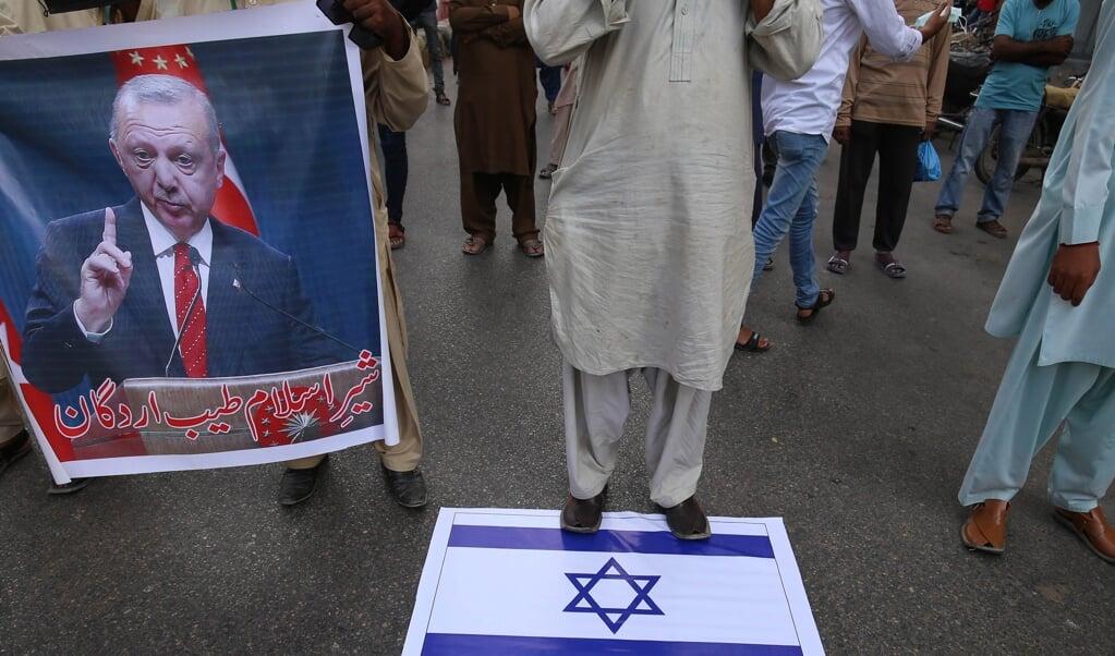 Demonstranten in Pakistan houden een portret van de Turkse president Erdogan vast, tijdens een protest tegen Israël. Turkije werpt zich op als verdediger van Palestijnse belangen in het oplaaiende conflict met Israël.  (beeld epa / Rehan Khan)