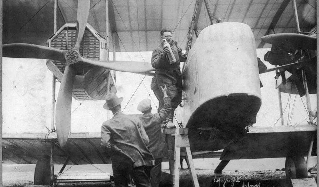 Piloot John Alcock laadt de laatste spullen in, kort voor zijn vertrek.  (beeld wikimedia)