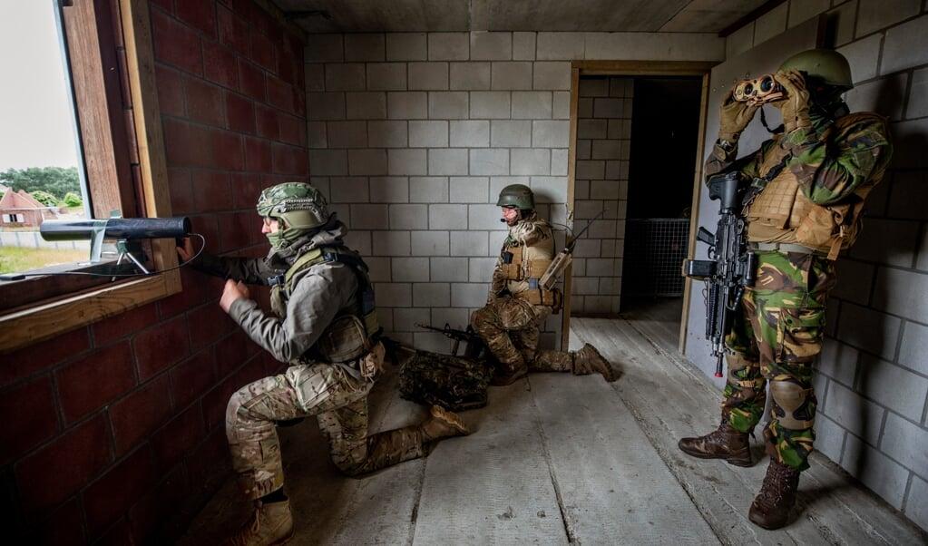 Militairen aan het werk met het cema sense drop device (links bij het raam) waarmee wifi, telefoon en andere digitale signalen worden onderschept.  (beeld Raymond Rutting)