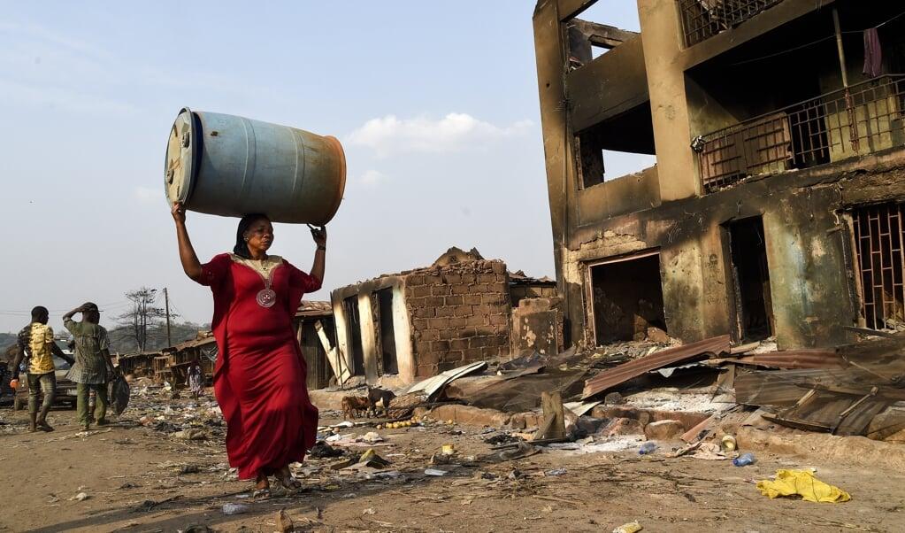 De bevolking van Ibadan zoekt naar bruikbare materialen in de door Fulani-herders platgebrande winkels.  (beeld Pius Utomi Ekpei / afp)