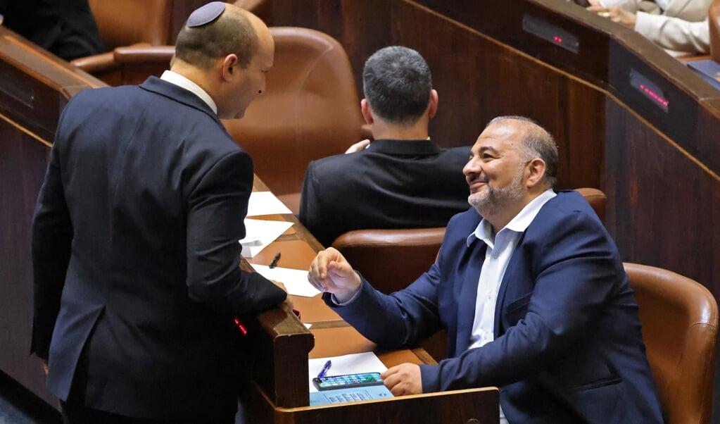 De nieuwe Israëlische premier Naftali Bennett (links) in gesprek met Mansour Abbas, leider van de Israëlisch-Arabische partij Ra'am (die ook deelneemt aan de coalitie).  (beeld afp / Emmanuel Dunand)
