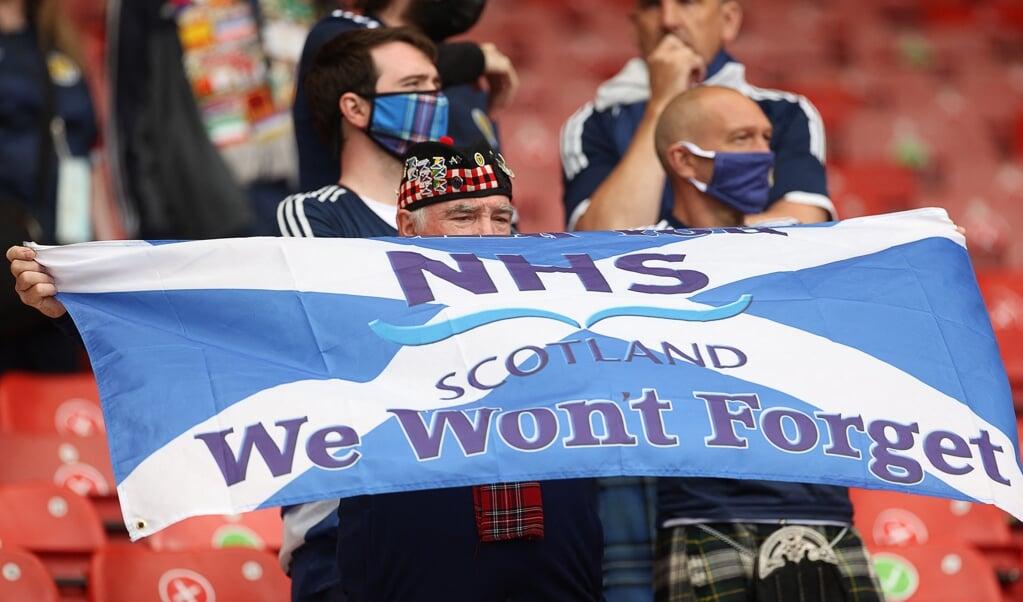 Schotse supporters bedanken de National Health Service voor de zorg in coronatijden.  (beeld afp / Lee Smith)