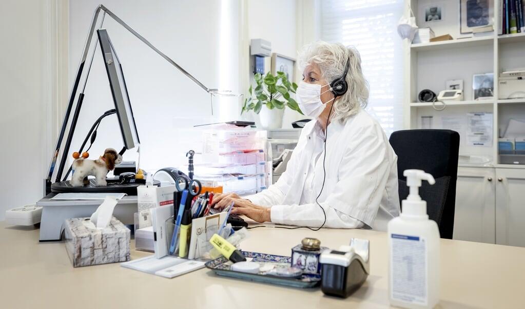 Een huisarts tijdens een online-consult met een patiënt.  (beeld anp / Koen van Weel)