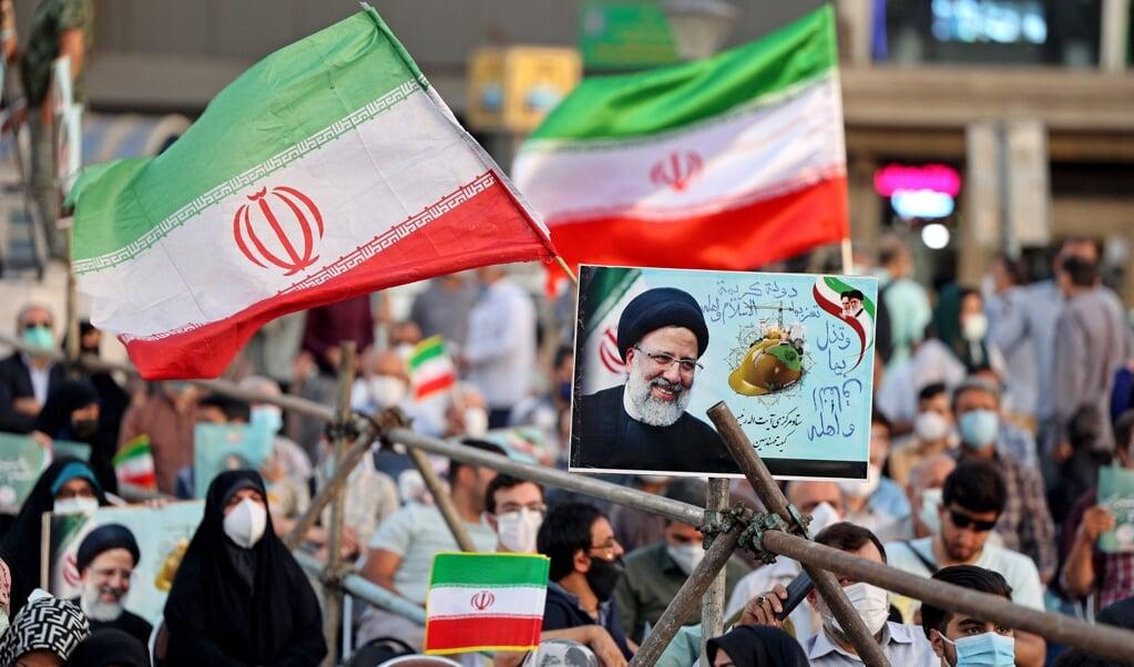 Vrijdag vinden in Iran verkiezingen plaats. Beeld: Aanhangers van de Iraanse kandidaat Ebrahim Raisi (de huidige opperrechter) voeren campagne voor hem in de hoofdstad Teheran.  (beeld afp / Atta Kenare)