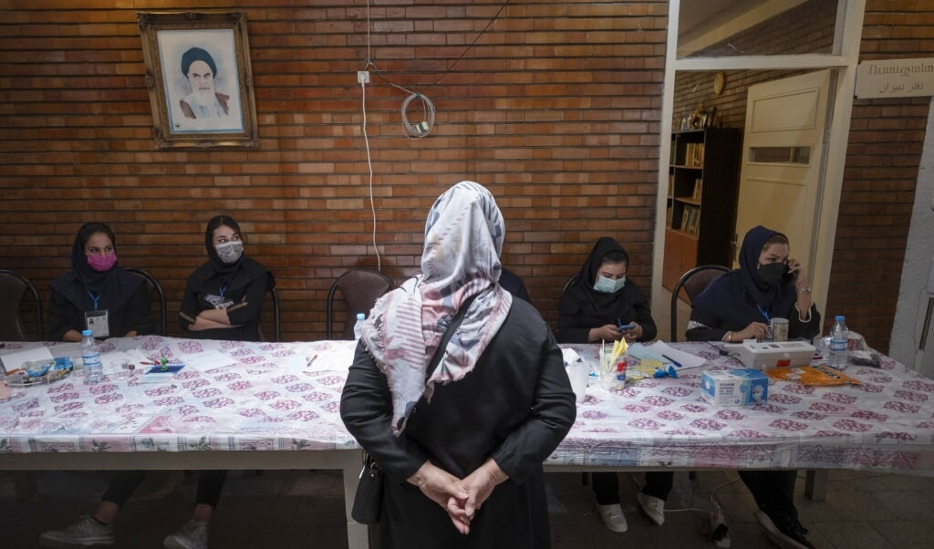 Een Iraanse christelijke vrouw wacht op haar registratie, voordat ze gaat stemmen in een christelijke school in Teheran.   (beeld afp / Morteza Nikoubazl)