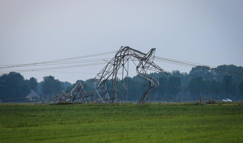 Een van de vier omgewaaide elektriciteitsmasten in het Gelderse Oosterwolde. Volgens de gemeente Oldebroek is de schade groot.  (beeld anp)
