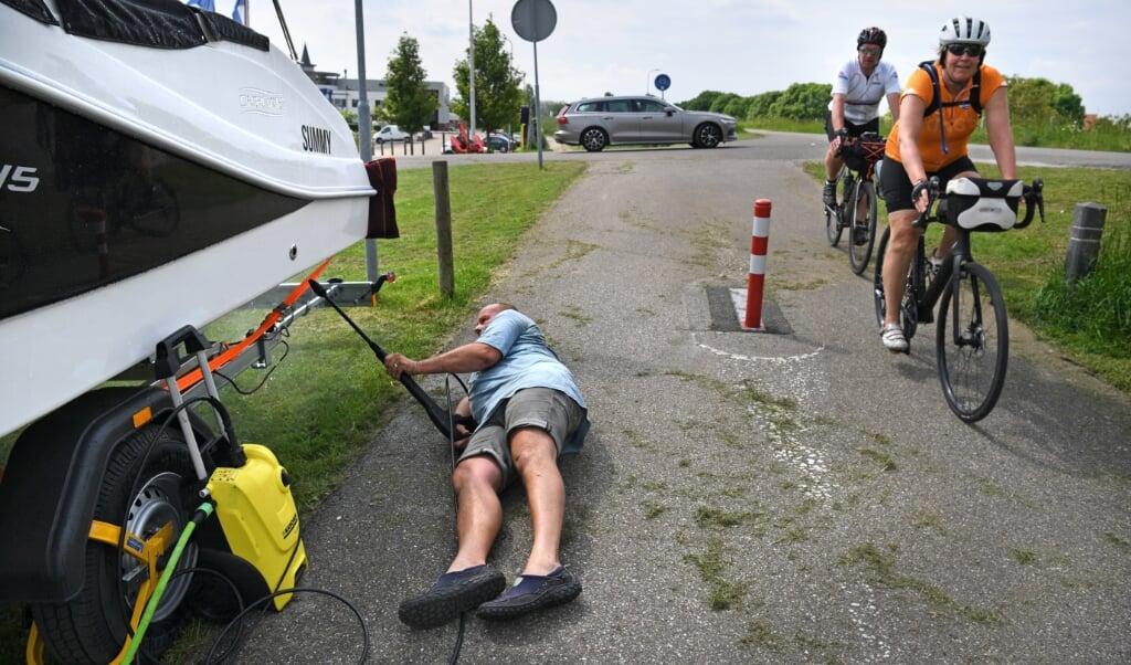 Een man maakt zijn boot schoon langs het fietspad.  (beeld Marcel van den Bergh)