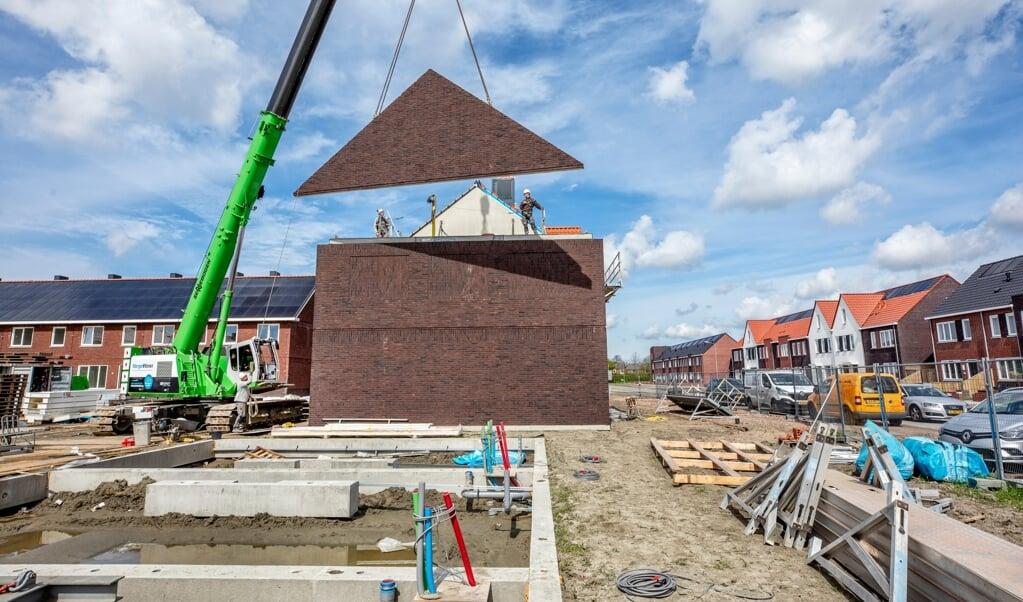 Met de kraan worden dakdelen op een woning in de Middelburgse wijk Mortiere gehesen.  (beeld Raymond Rutting)