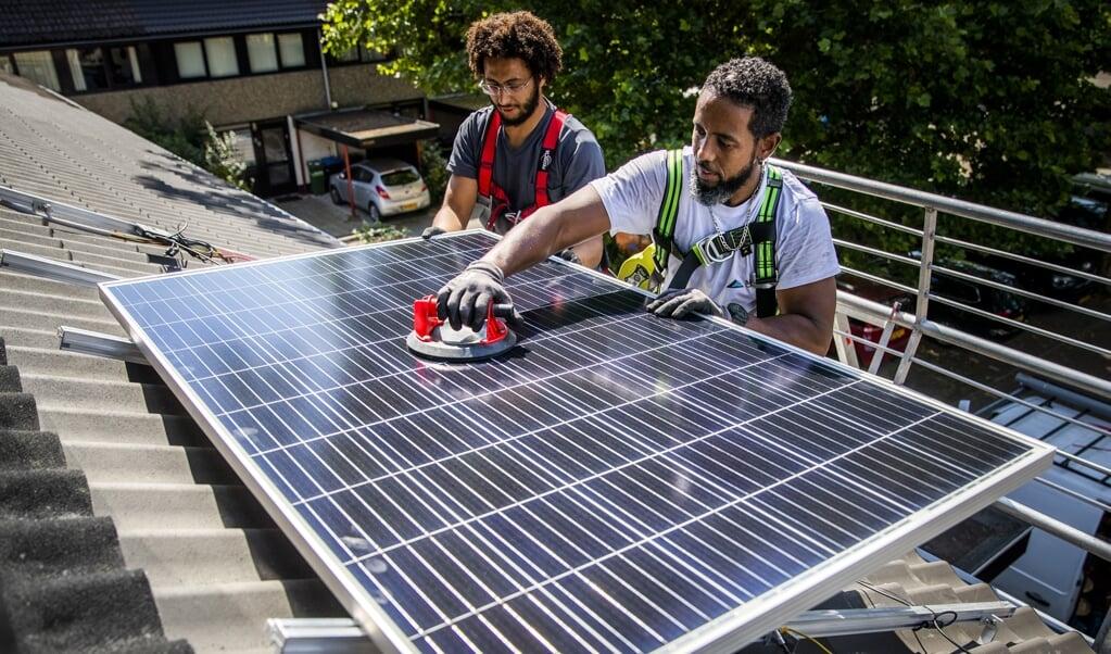 Een installateur plaatst zonnepanelen op het dak van een woonhuis.  (beeld anp / Remko de Waal)