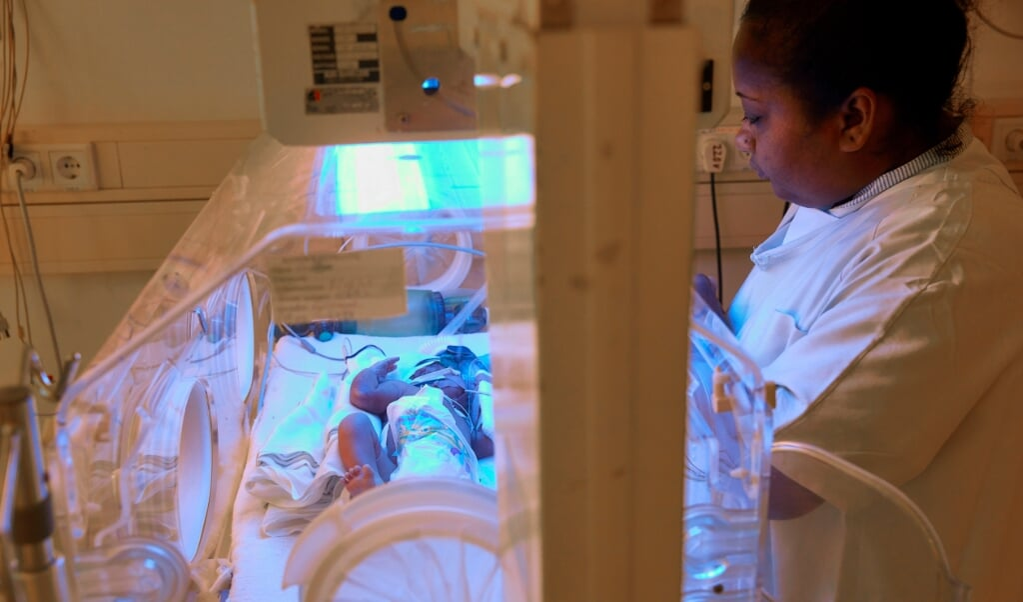 Een verpleegkundige verleent zorg aan een baby in een couveuse in het Diakonessenhuis in Paramaribo.  (anp / Jaco Klamer)