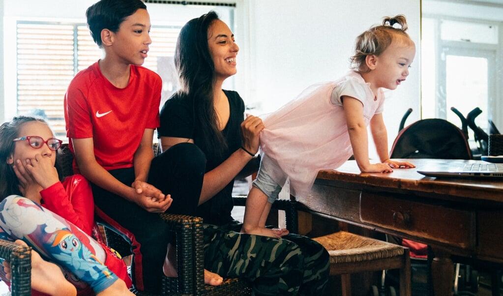 Melody en kinderen videobellen met haar partner in de gevangenis.  (beeld Rebecca Fertinel)