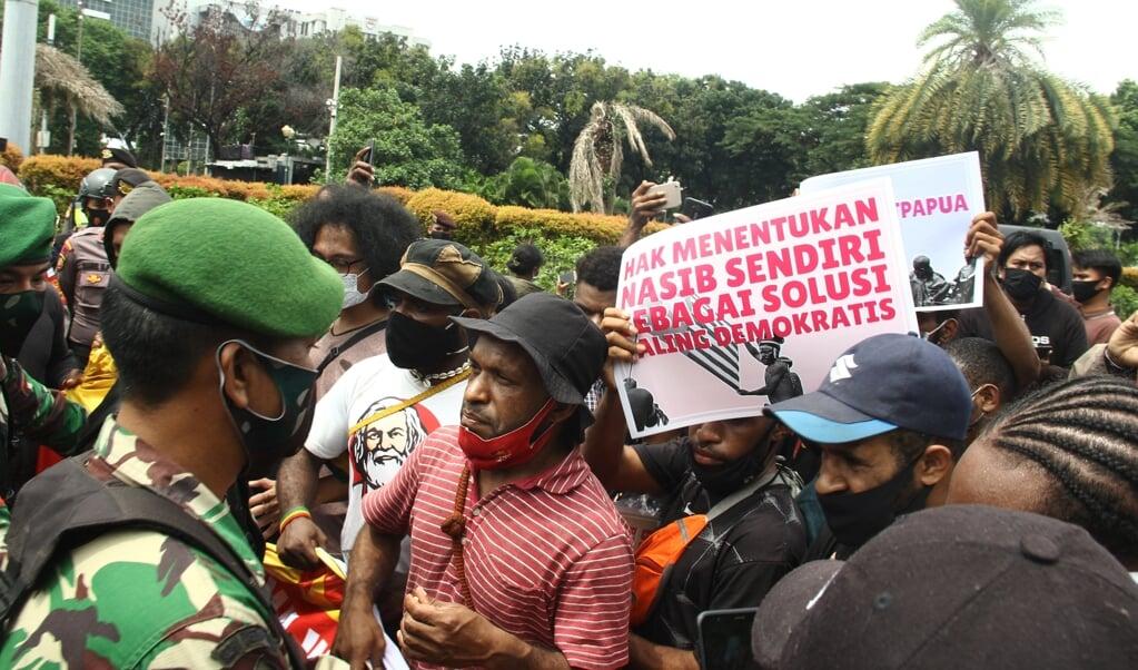 Voorstanders van een onafhankelijk Papua demonstreren onder streng toezicht van de autoriteiten in de Indonesische hoofdstad Jakarta, december 2020.  (beeld afp / Dany Krisnadhi)