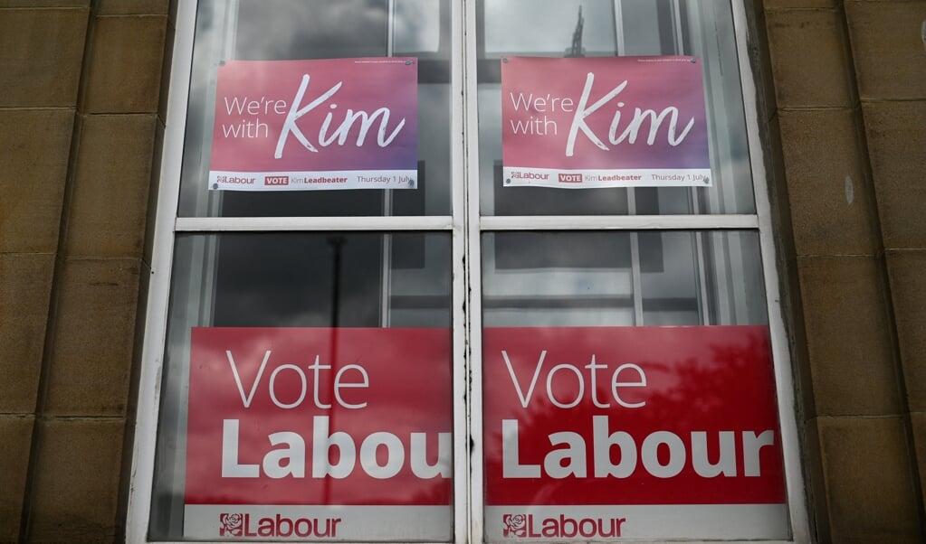 Een Labour-aanhanger heeft voor haar raam in Batley posters opgehangen voor kandidaat Kim Leadbeater, zus van de vermoorde politica Jo Cox. In het arbeidersstadje woedt een felle stembusstrijd op links.  (beeld afp / Oli Scarff)