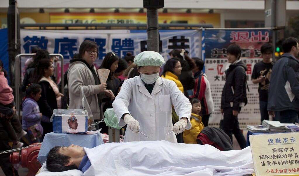 Leden van de Falun Gong-beweging protesteren verkleed tegen gedwongen 'orgaanoogst' op het station van Hongkong in 2012.  (beeld epa / Jerome Favre)