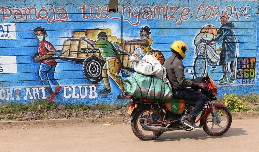 Samen vechten we tegen corona, staat op een muur in Nairobi, Kenia.  (beeld afp / Simon Maina)