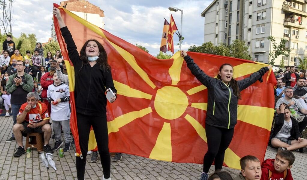 Supporters met de vlag van Noord-Macedonië tijdens het duel met Oostenrijk.  (beeld afp / Robert Atanasovski)